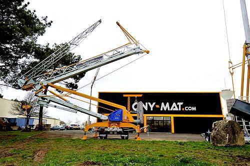 La grue Potain IGO M14 en cours de déploiement sur la terrasse du magasin Tony-Mat Grues à Vannes, Bretagne.